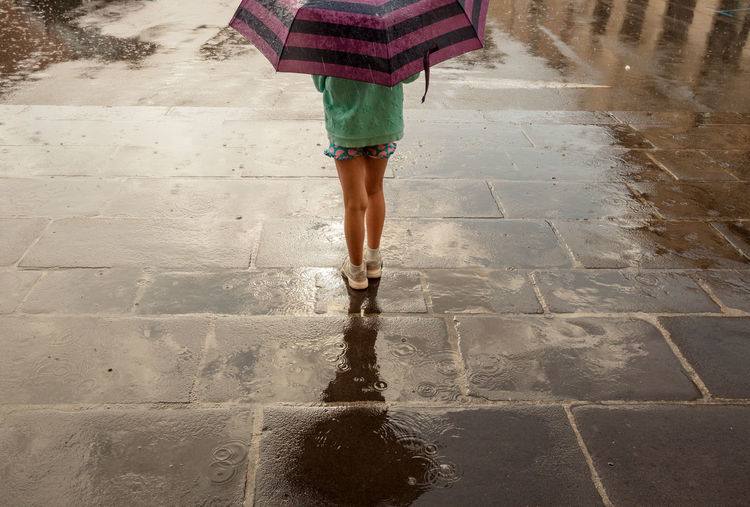 Low section of woman standing on wet footpath