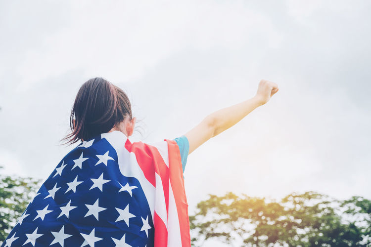 Low angle view of girl with american flag standing against sky