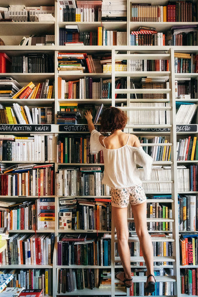 Young woman stands back on ladder and reaches for book on shelf in bookstore Book Bookshelf Childhood Choice Education Hair Indoors  Ladder Library One Person Publication Rear View Shelf Standing Studying Women