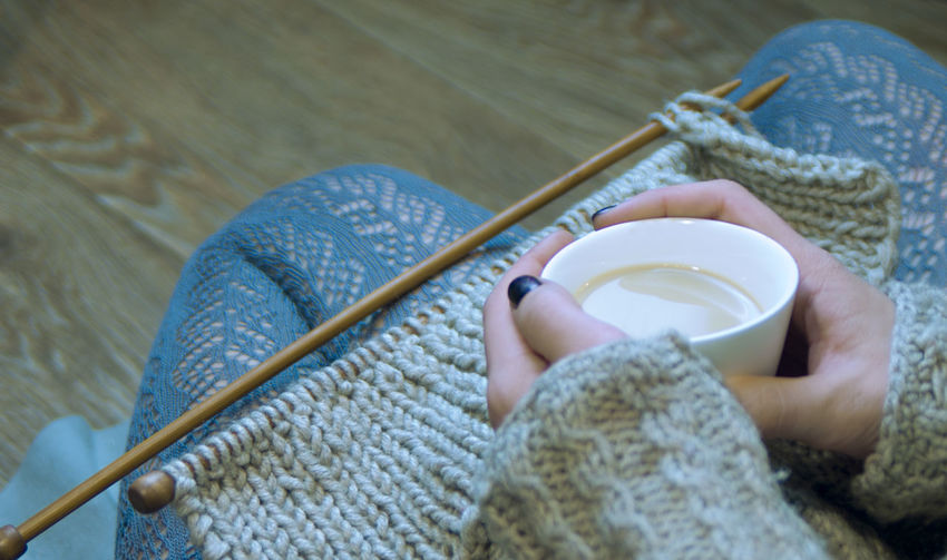 a young woman knits on the spokes and drinks coffee Weaving Ajurno Lace Knitting Cozy Hands Home Knitted Sweater Openwork Text Background Woman Coffee Time Copy Space Craft Gray Hand Holding Hot Drink Human Hand Indoors  Keep Warm Lace Lace - Textile Openwork Textile Wool