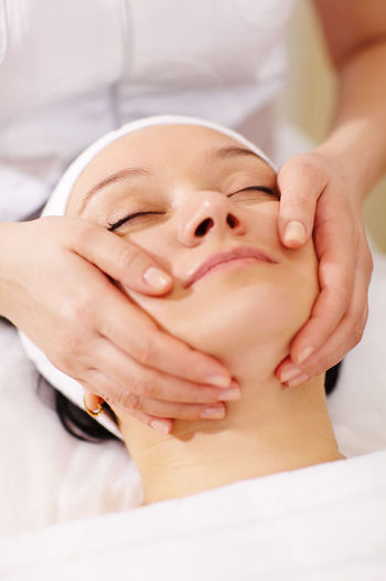 Beautician doing facial massage of customer