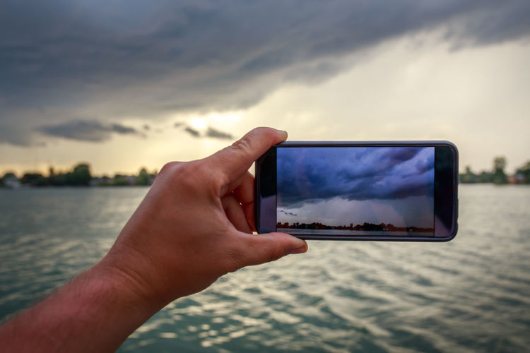 Cropped Hand Of Man Photographing Cloudy Sky From Smart Phone During Sunset