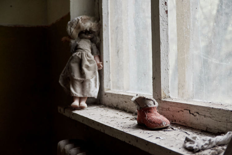 Statue with toy on window sill