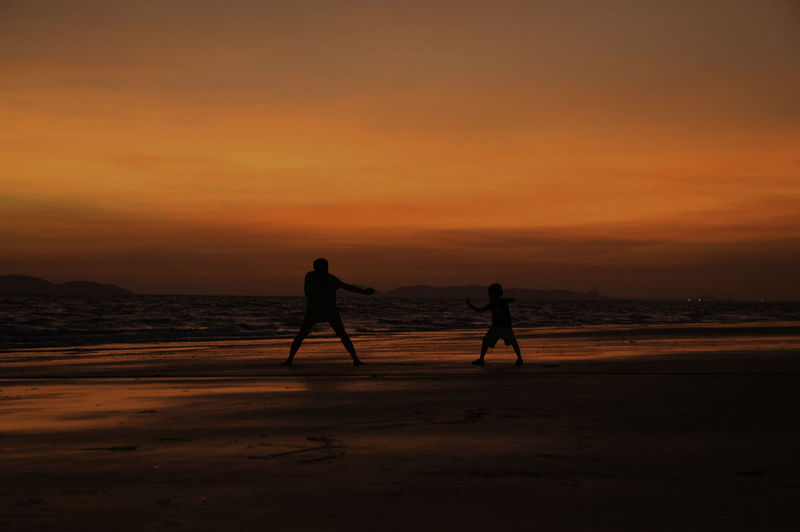 Silhouette Father And Son Playing At Beach Against Orange Sky