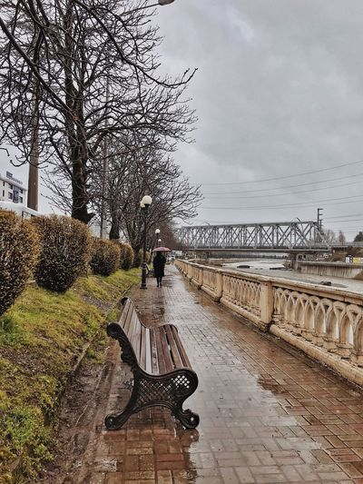 View of park bench by bridge against sky