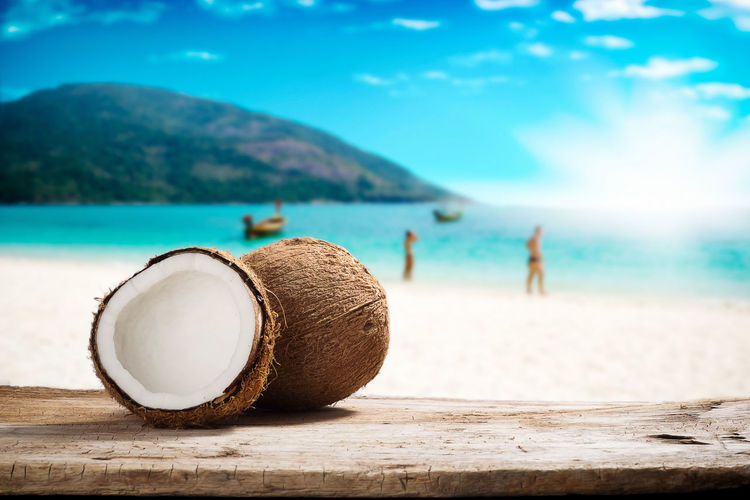 Fruits of coconuts on desk space. Coconut Copy Space Beach Beauty In Nature Focus On Foreground Fruits Holiday Incidental People Land Mountain Nature Outdoors Sand Sea Seascape Sky Space Sunlight Sunny Day Water Wooden Desk