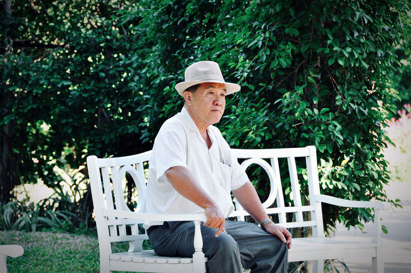 Side view of man sitting on seat against trees in the garden