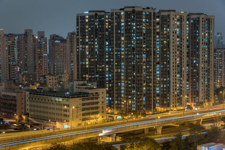 Illuminated apartment skyscrapers in city at night