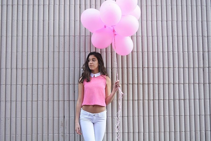 Portrait of young woman with pink balloons