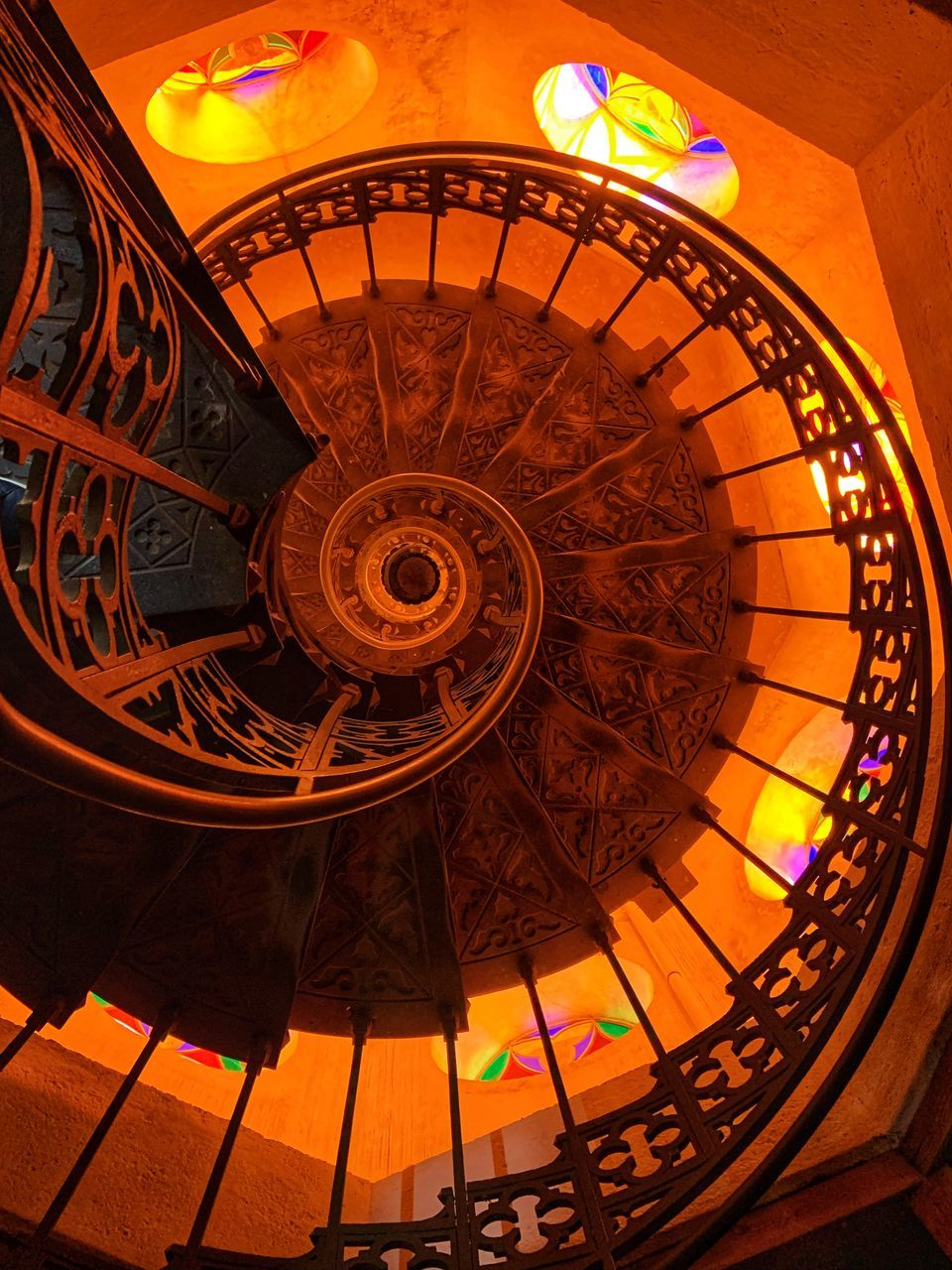 architecture, built structure, indoors, staircase, pattern, steps and staircases, illuminated, no people, railing, spiral, building, travel destinations, low angle view, spiral staircase, design, directly below, ceiling, travel, tourism, ornate