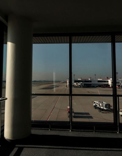 View of airport runway seen through airplane window