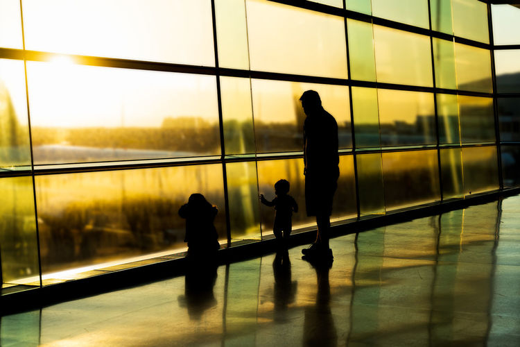 Silhouette people standing by glass window at airport