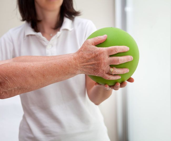 Senior patient undergoing rehabilitation with a green ball Center Care Arms Medical Help Hospital Gym Therapy Patient Physiotherapy Therapist Medicine Geriatrics Senior Woman Rehabilitation One Person Women Adult Lifestyles Indoors  Human Body Part Mid Adult Healthy Lifestyle Wellbeing Human Hand Real People Focus On Foreground Holding Mid Adult Women Front View