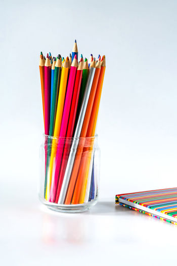 Close-up of multi colored pencils on table against white background