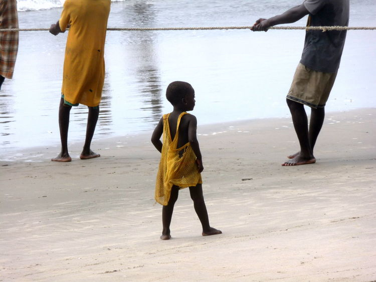 Adults African Beach Child Children Cute Different Perspective Fishing Net Little Girl Sand Developing Country Barefoot Yellow Working Hard Showcase June Street Photography Travel Photography Travel Destinations Faces Of Africa Children Of The World