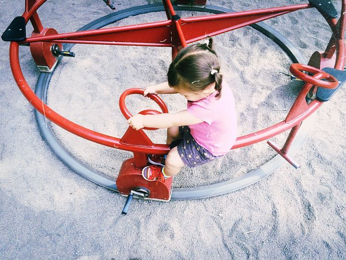 High angle view of girl on roundabout in playground