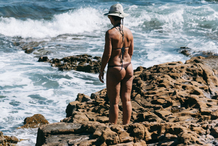 Rear view of mature woman in bikini standing on rocky shore