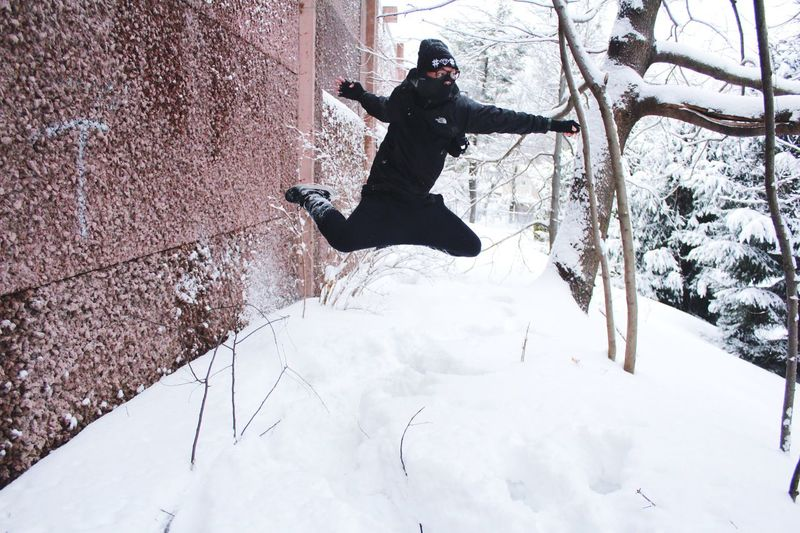 Person Kicking In The Air Above Snow Ground