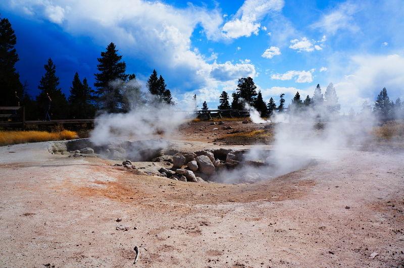 Steam emitting from hot springs against sky