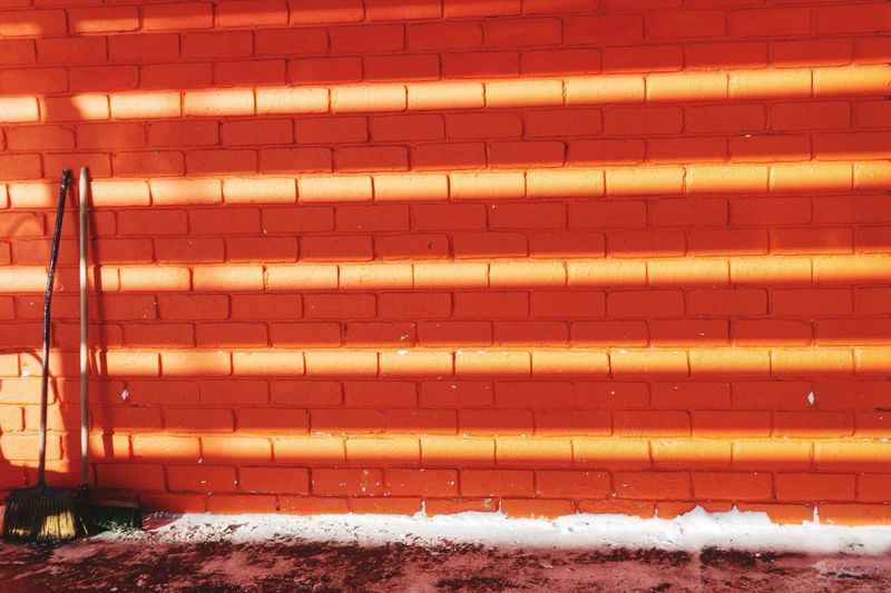 Snow covered brick wall, shadows play and sunlight
