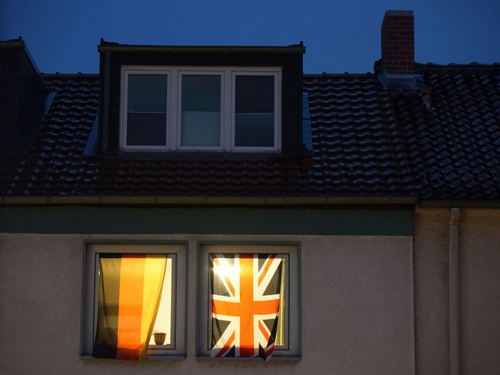 German And English Flags On Window Of House