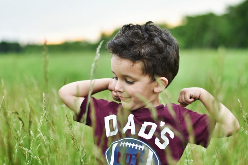 Cute boy flexing muscles while standing amidst plants on field