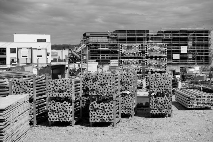 Stack of firewood by buildings in city against sky