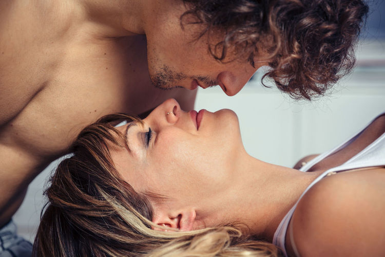 Closeup of young man kissing to beautiful woman lying over a bed. Love and couple relationships concept. Bed Couple Horizontal Intimate Kiss Love Man Relaxing Romance Romantic Woman Young Attractive Caucasian Closed Eyes Curly Hair Desire Female Liying Male Passion Portrait Sensuality Photo Sleep Togetherness