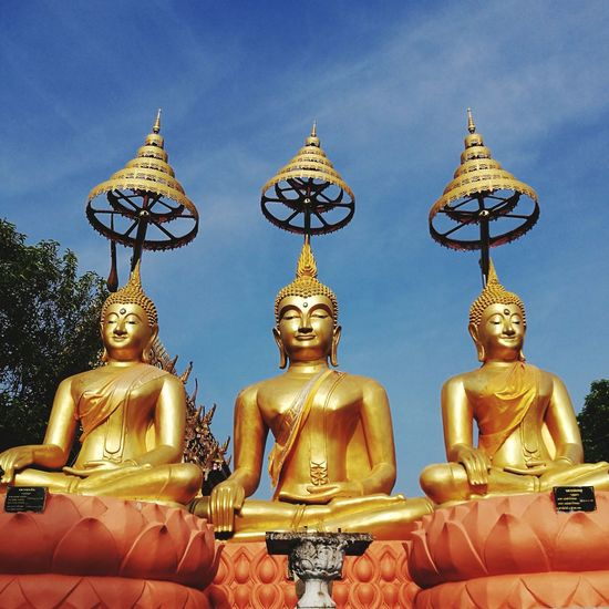 Low angle view of golden buddha statues against blue sky