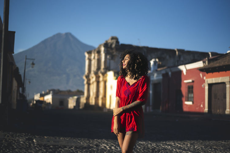 Woman Standing Against Houses And Mountains