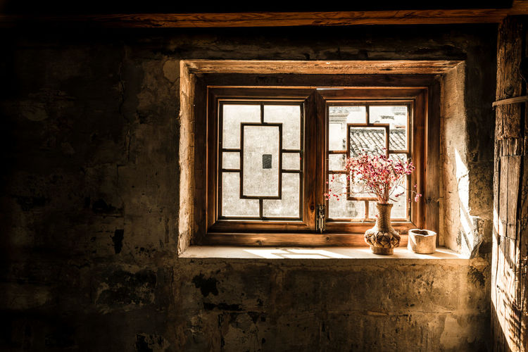 Flower vase on window sill in old house