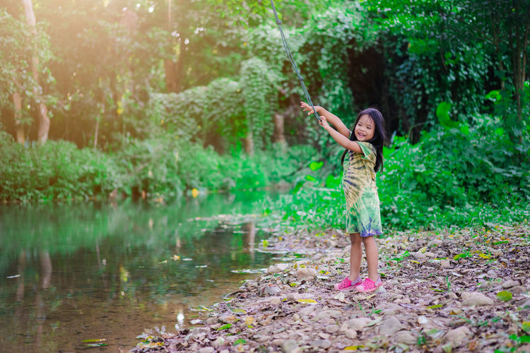Cute girl smiling holding rope swing while standing by lake