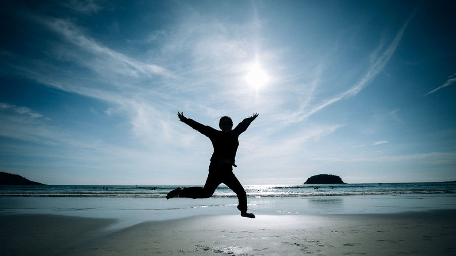 Full length of silhouette woman jumping at beach against sky