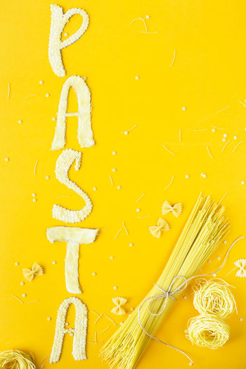 The word pasta is laid out in bulk letters from small raw macaroni on a yellow background next to a variety of kinds of pasta. Food on a bright background Cooking Dinner Italian Pasta Raw Food Food And Drink Italian Food Kitchen No People Pasta Pasta Time Spagetti Still Life Uncooked Uncooked Pasta Yellow