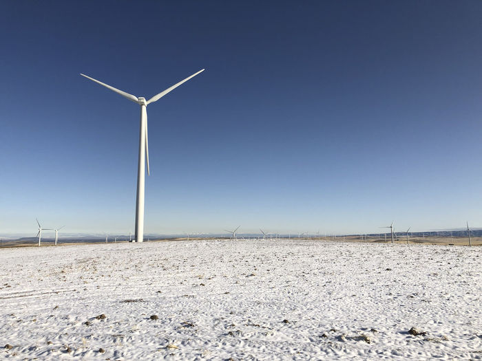 Windmill on field against clear sky