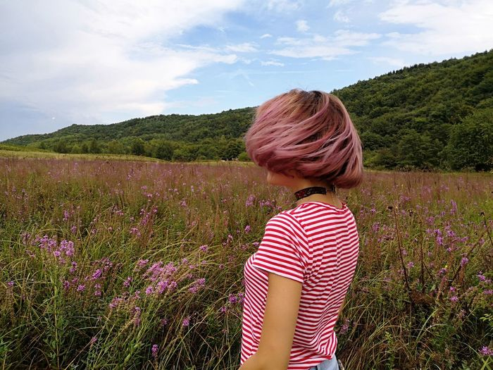 Side View Of Mid Adult Woman With Short Hair Standing On Grassy Field Against Sky