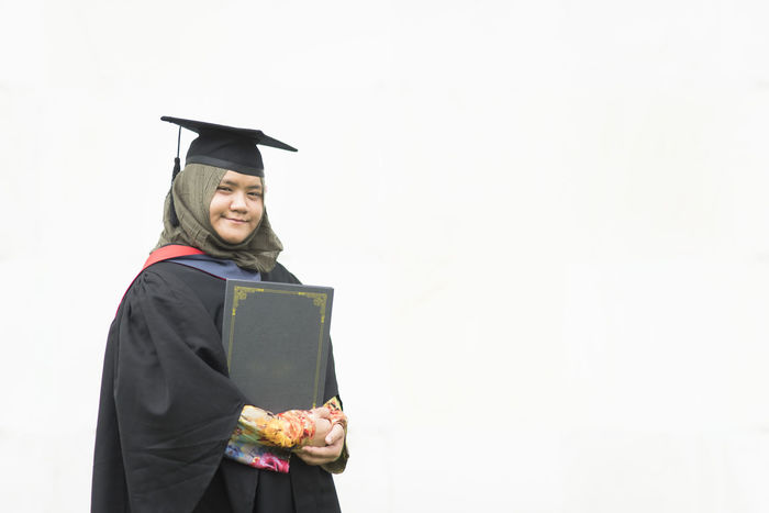 education concept - young woman holding a degree certificate with smiling face isolated on a white background Student Woman Young Achievement Celebration Ceremony College Concept Day Degree Diploma Education Future Graduate Graduation Graduation Gown Happiness Holding Knowledge Life Events Mortarboard People Pride University University Student