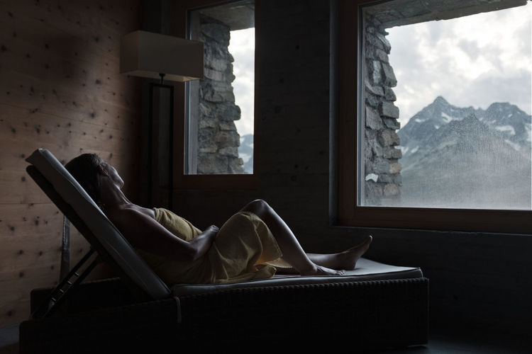 Man resting on chair by window at home