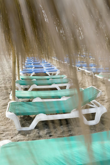 Beach Parasol Empty Beach Deserted Beach Deserted Straw Parasol Straw SPAIN Motion Water No People Day Seat Nature Blurred Motion Chair Selective Focus Outdoors Wood - Material Absence Blue Long Exposure Empty Swimming Pool Turquoise Colored