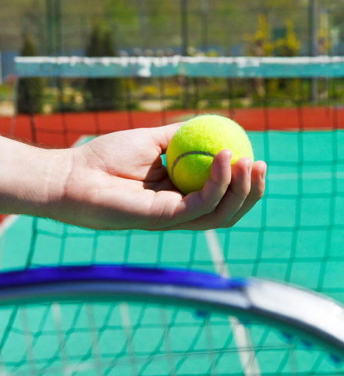 Cropped hand of person holding tennis ball