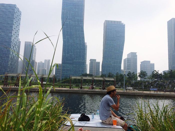 Side View Of Man Sitting On Jetty In River Against Skyscrapers
