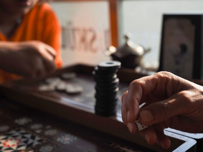 Cropped Image Of Man Hand Holding Dices While Playing Game
