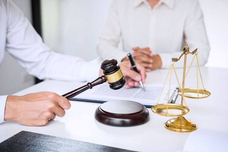 Male Lawyer Sitting With Customer At Desk In Office