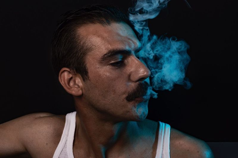 Close-Up Of Young Man Smoking While Standing Against Black Background