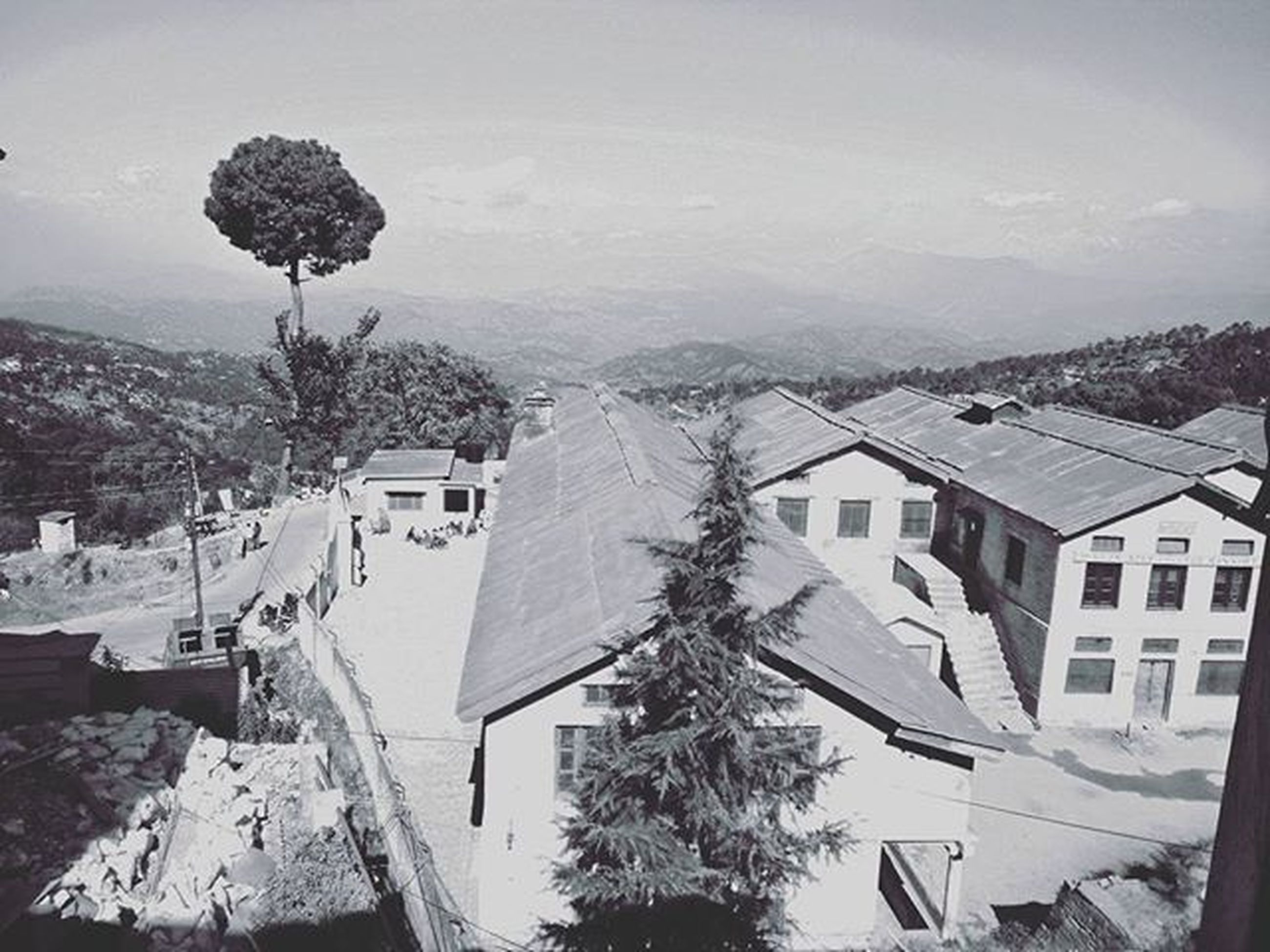 snow, winter, building exterior, cold temperature, architecture, house, built structure, residential structure, season, mountain, tree, residential building, high angle view, sky, weather, town, roof, covering, landscape, nature