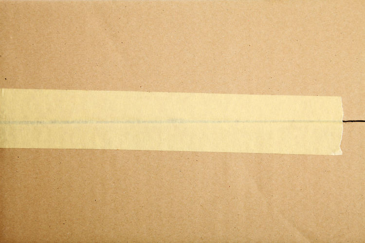 Directly above shot of adhesive tape on cardboard box