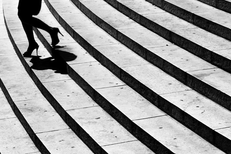 Low section of woman moving down on steps