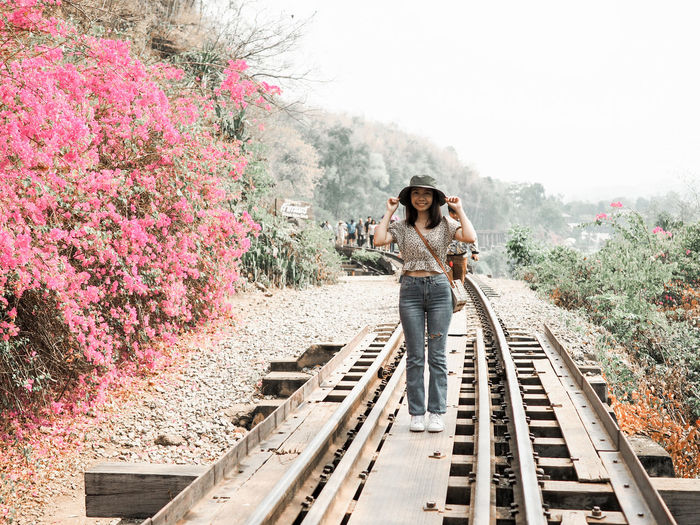Portrait of young woman standing on railroad track
