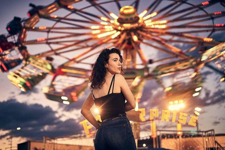 Portrait of woman with illuminated ferris wheel