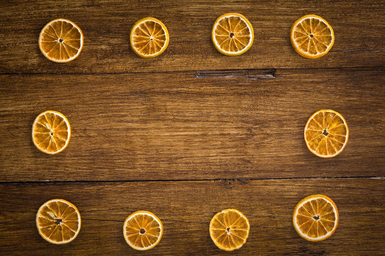 Dried orange slices form a frame on a wooden table Table Orange Dried Circle Frame Food Fruit Decorative Festive SLICE Wood Copy Space Close-up Shape In A Row Christmas Border Directly Above Backgrounds Recipe Citrus Fruit Celebration Holiday Seasonal Rustic